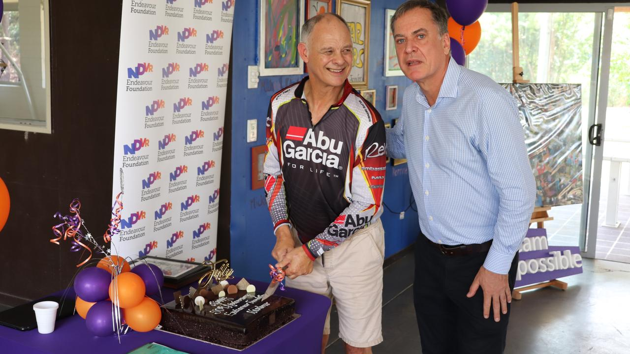 Michael Clark (a customer of 50 years with Endeavour Foundation) cuts the cake with Endeavour Foundation CEO Andrew Donne. Picture: Contributed