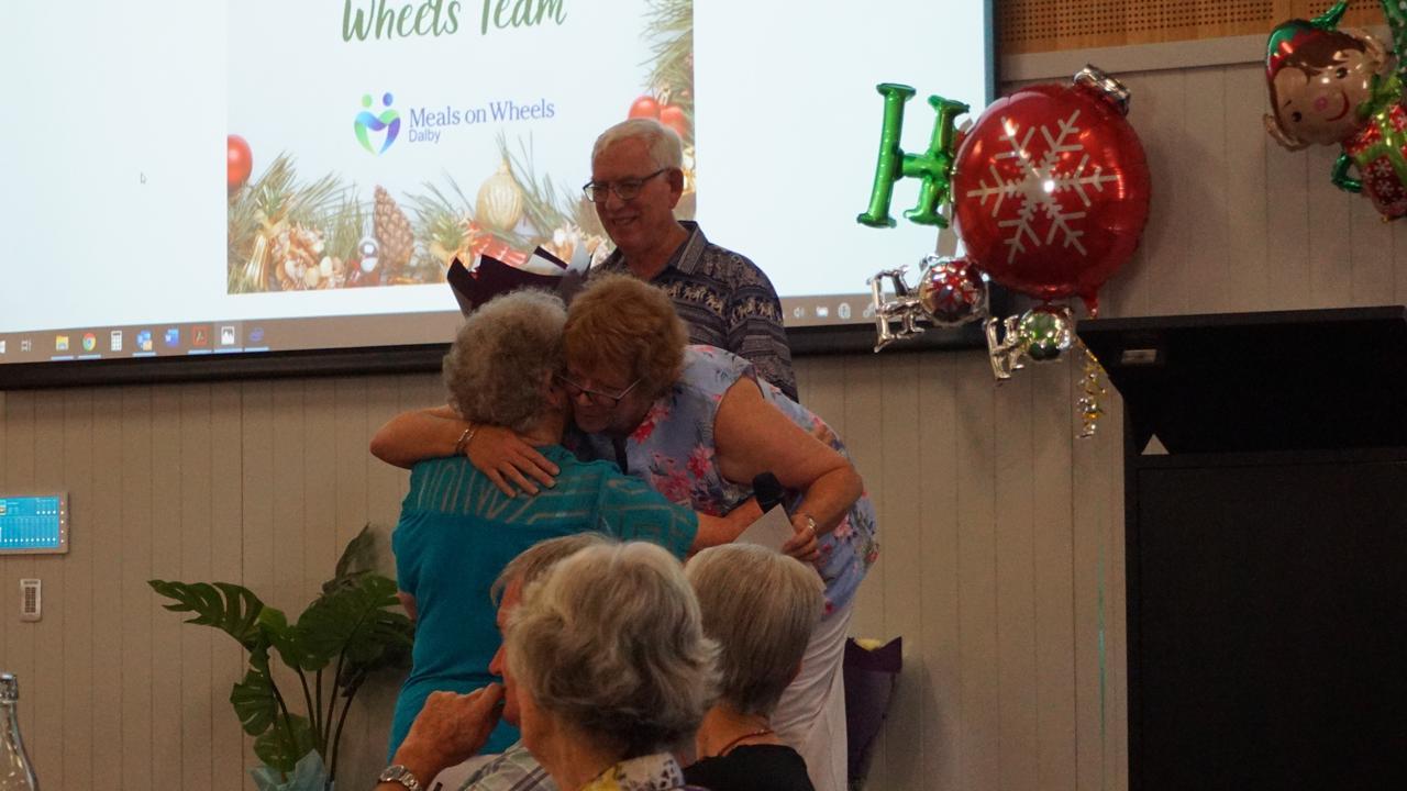 Bob Cook on stage, Margaret Mott hugging Jocelyn Milne, one of the volunteers now on the honour roll.