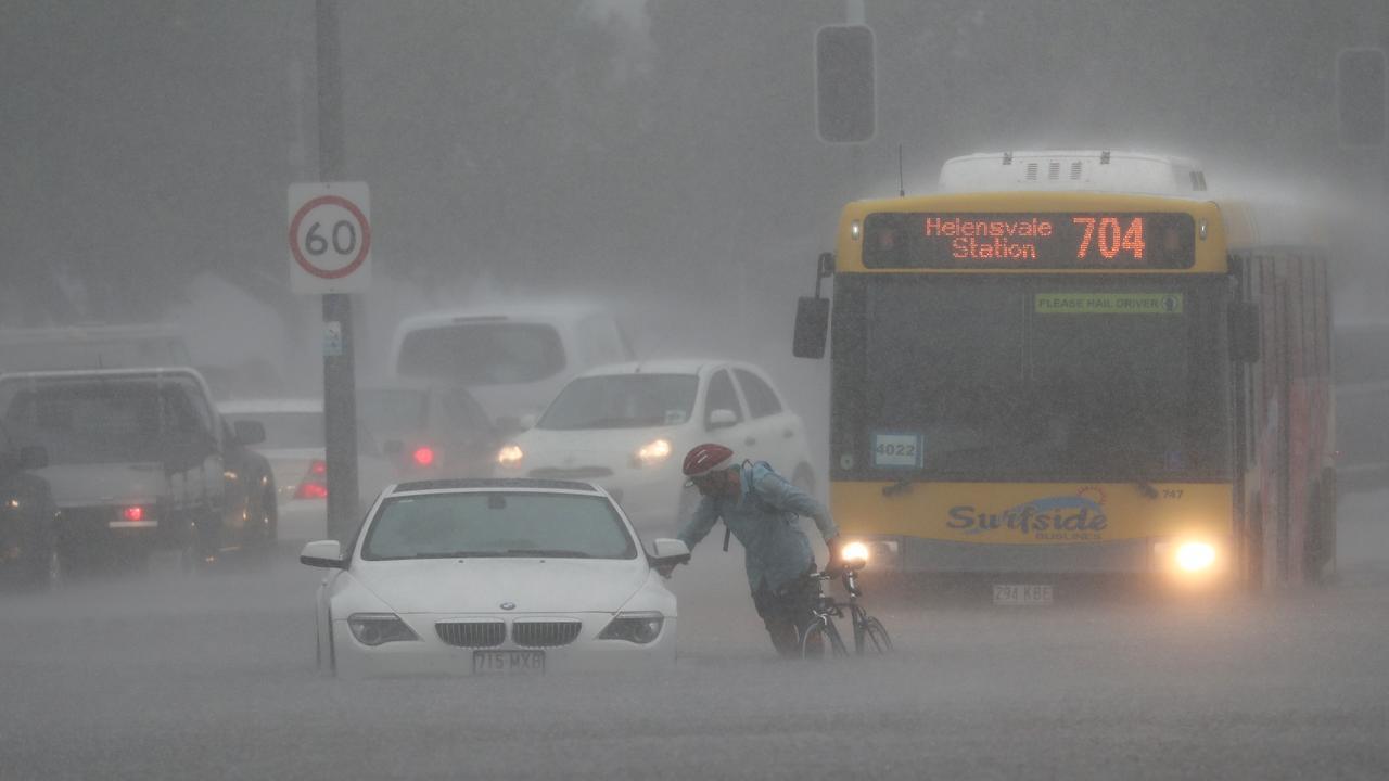 A cyclist makes their way through the flood water. Picture: Jason O'Brien