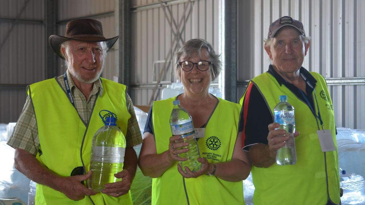 HELPING EACH OTHER: Roy Waites, Sally Edwards and Greg Bell with water donations.