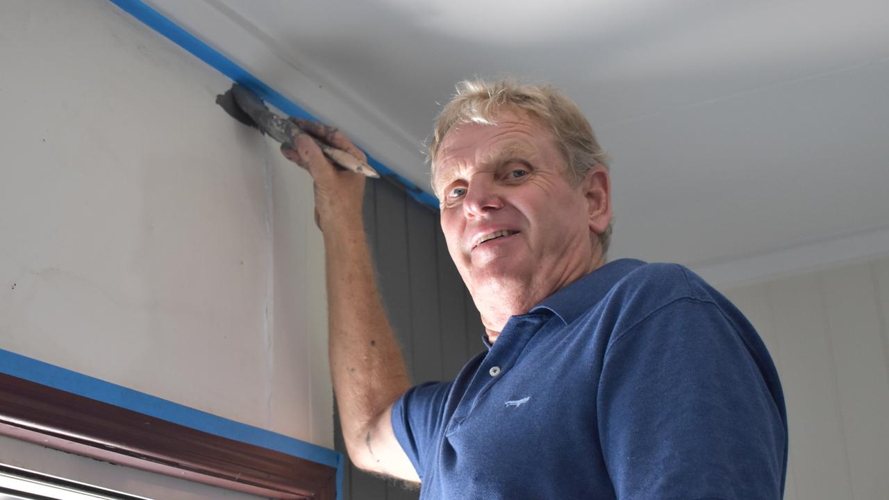 Rolf Mueller rushes to get the paint on before it dries as he renovates The Australian Hotel on a super-hot day in Gympie.