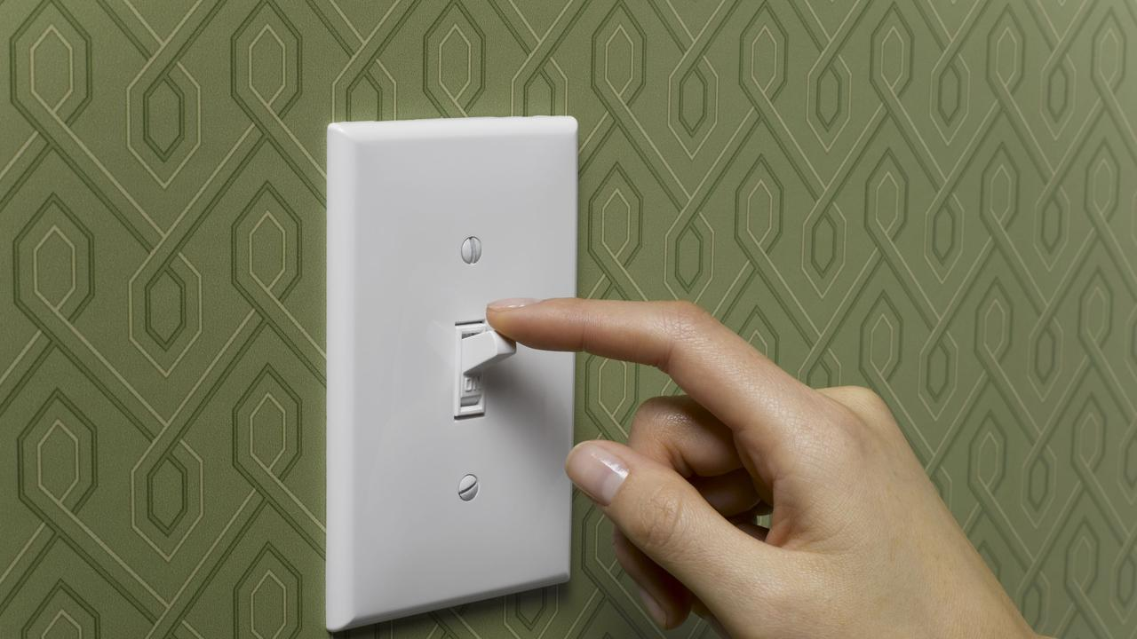Thinkstock image - Woman turning off light switch on green wallpapered wall, close-up