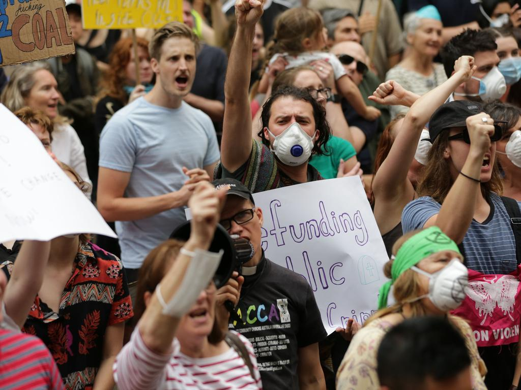 Crowds flooded the street, signs and face masks in hand. Picture: Christian Gilles