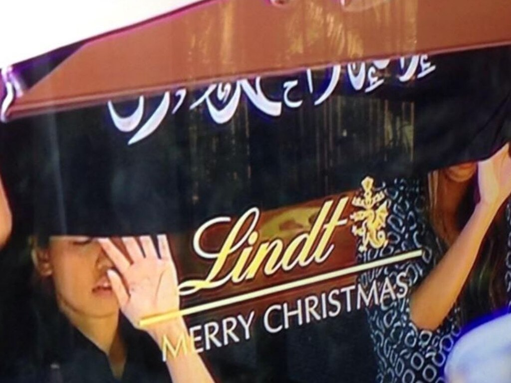 Hostages were forced to hold a flag in the window of the Lindt Cafe throughout the day.