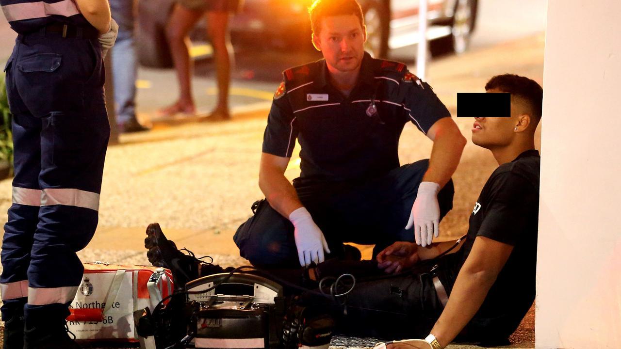 Paramedics help a man. Photo: AAP Image/Richard Gosling