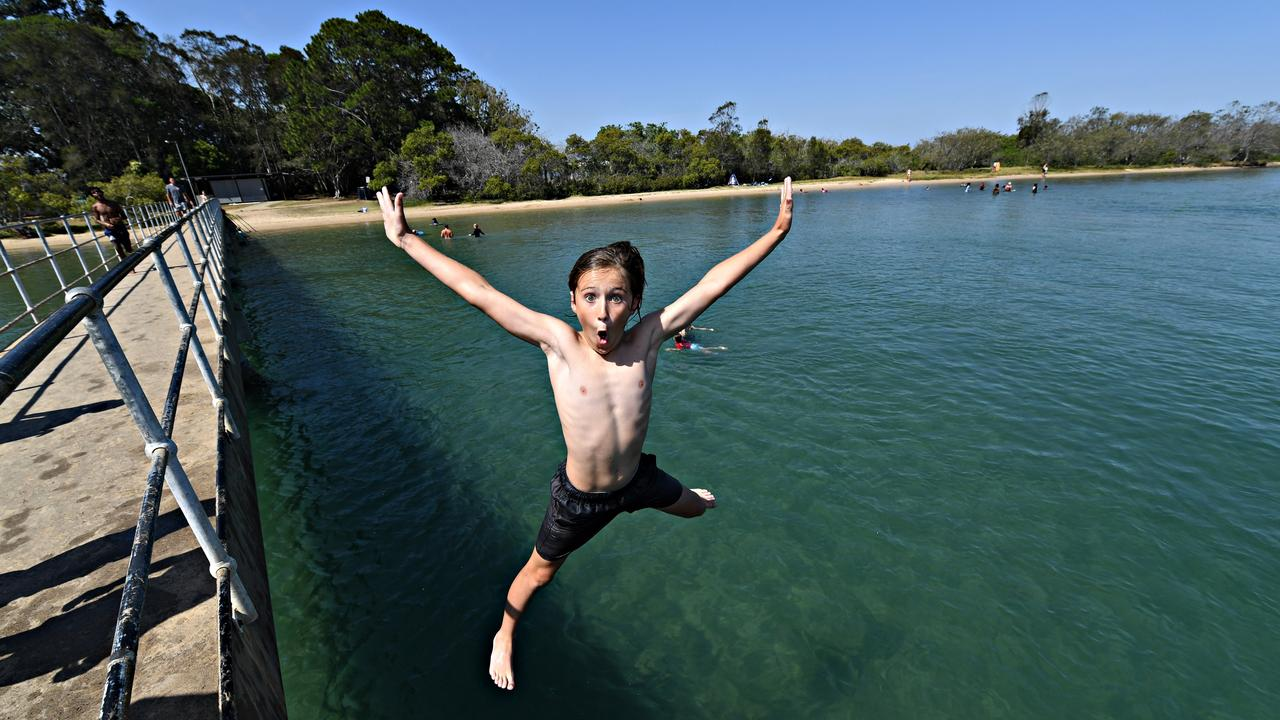 Riley Robinson didn't wait for the southerly change to cools down. He found both fun and comfort jumping from the Chambers Island foot bridge into the Maroochy River.