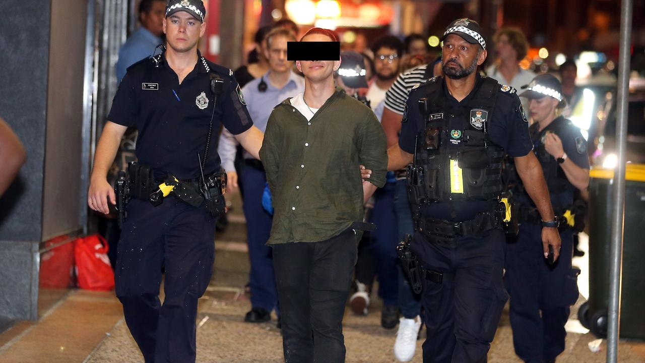 One reveller walks proudly while being led by police in Fortitude Valley. Photo: AAP Image/Richard Gosling