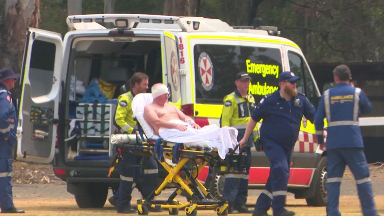 A male firefighter is loaded into a Careflight chopper after sustaining injuries during the Bargo bushfires. Picture: TNV