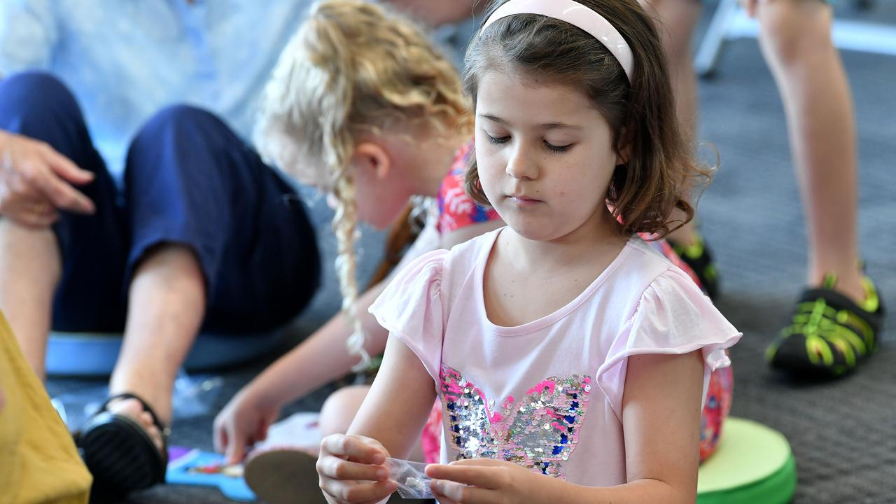 Asher Brodie, 7, concentrates on her Christmas art at the Dudley Denny City Library. Picture: Tony Martin