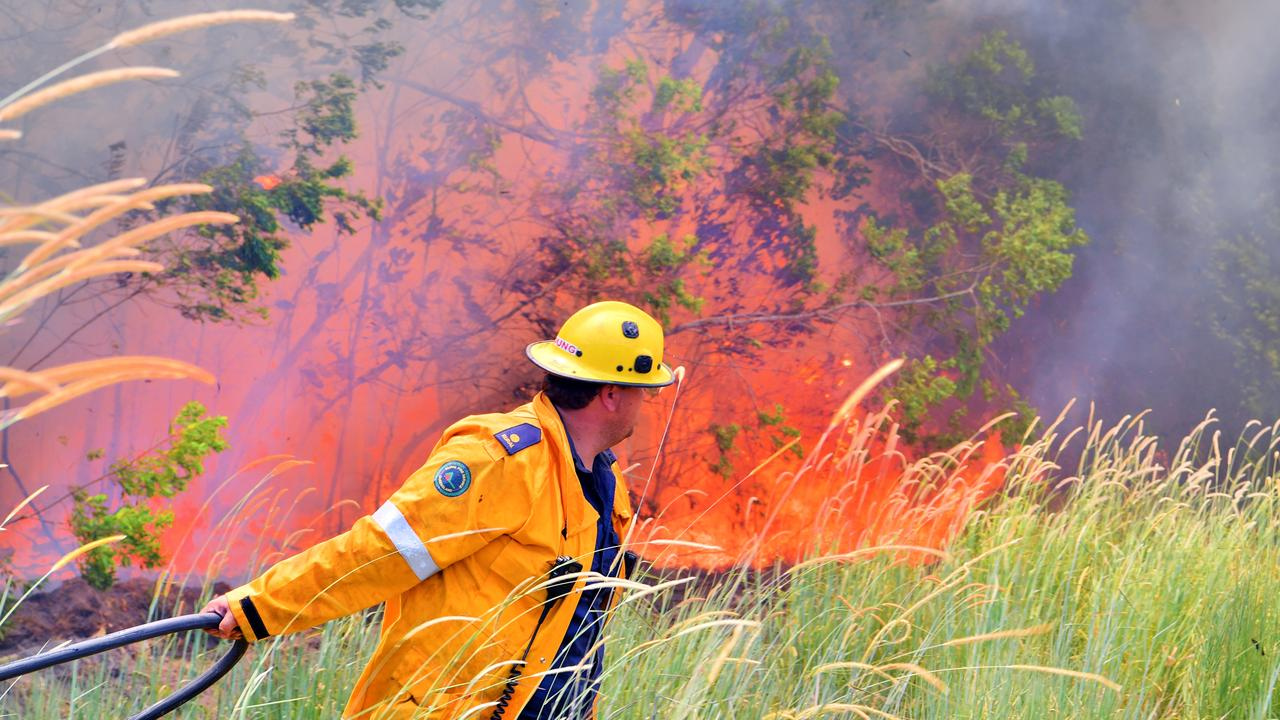 Hot, heavy work. A firefighter drags a hose into the seat of the blaze at Peregian Springs. Photo: John McCutcheon / Sunshine Coast Daily