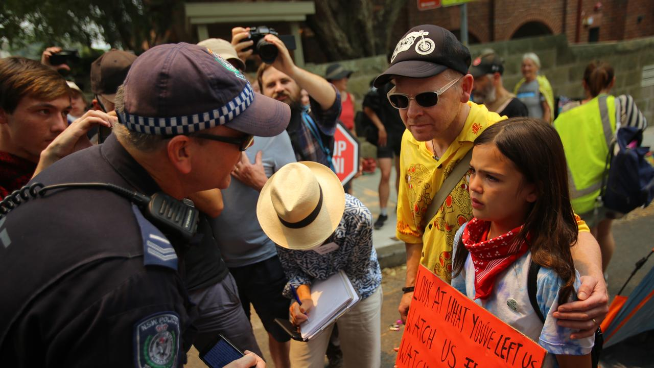 The young girl who went viral after footage of police threatening to arrest her father during a protest outside Kirribilli House has spoken out. Picture: AAP Image/Steven Saphore