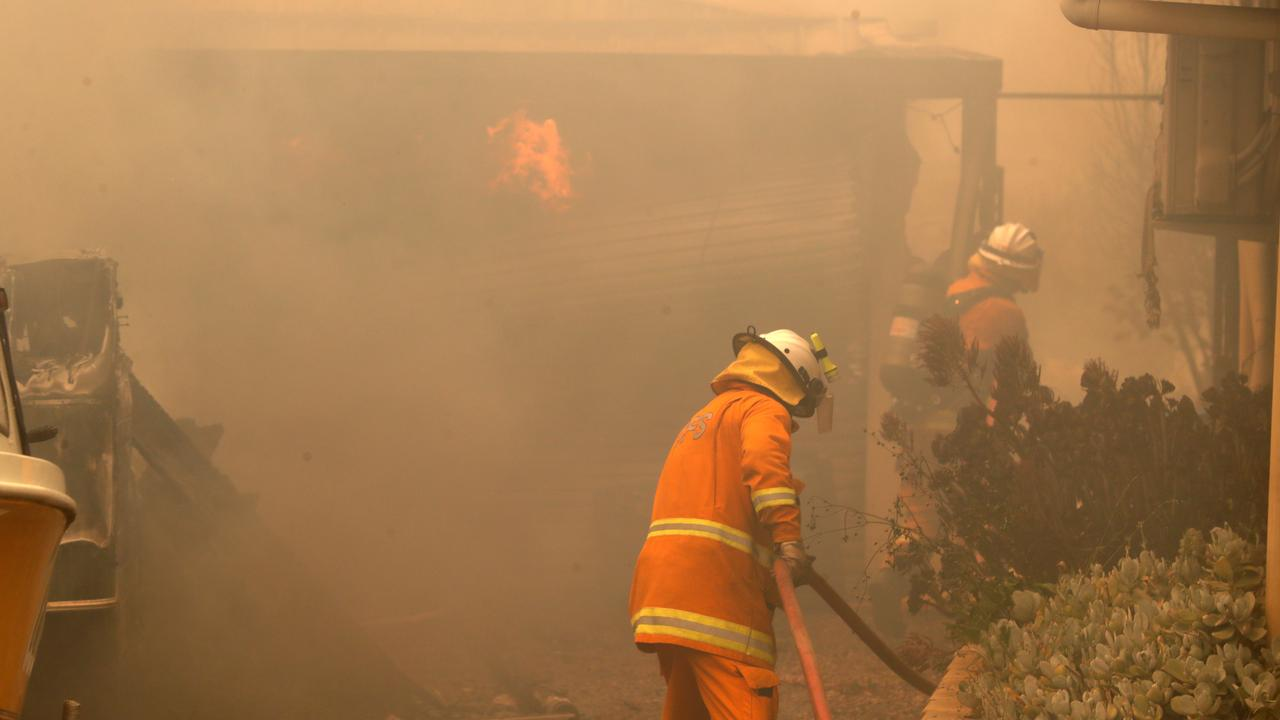 CFS firefighters put out fires on Jacaranda Drive at Woodside in the Adelaide Hills. Picture: AAP/Kelly Barnes
