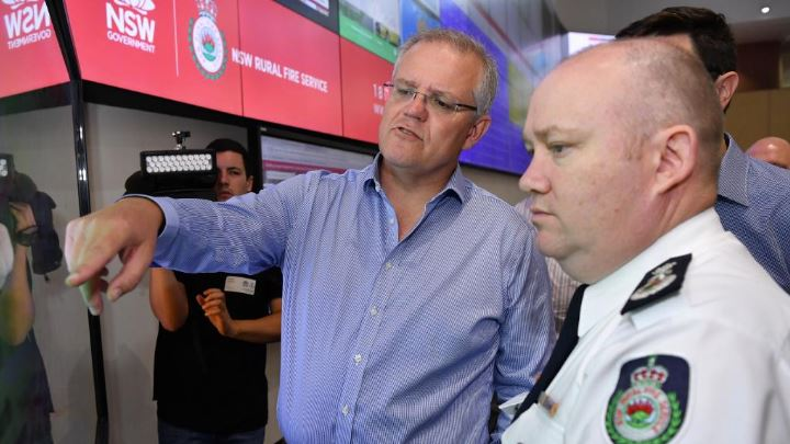 Prime Minister Scott Morrison is briefed by NSW RFS Commissioner Shane Fitzsimmons in the NSW Rural Fire Service control room in Sydney. Picture: AAP