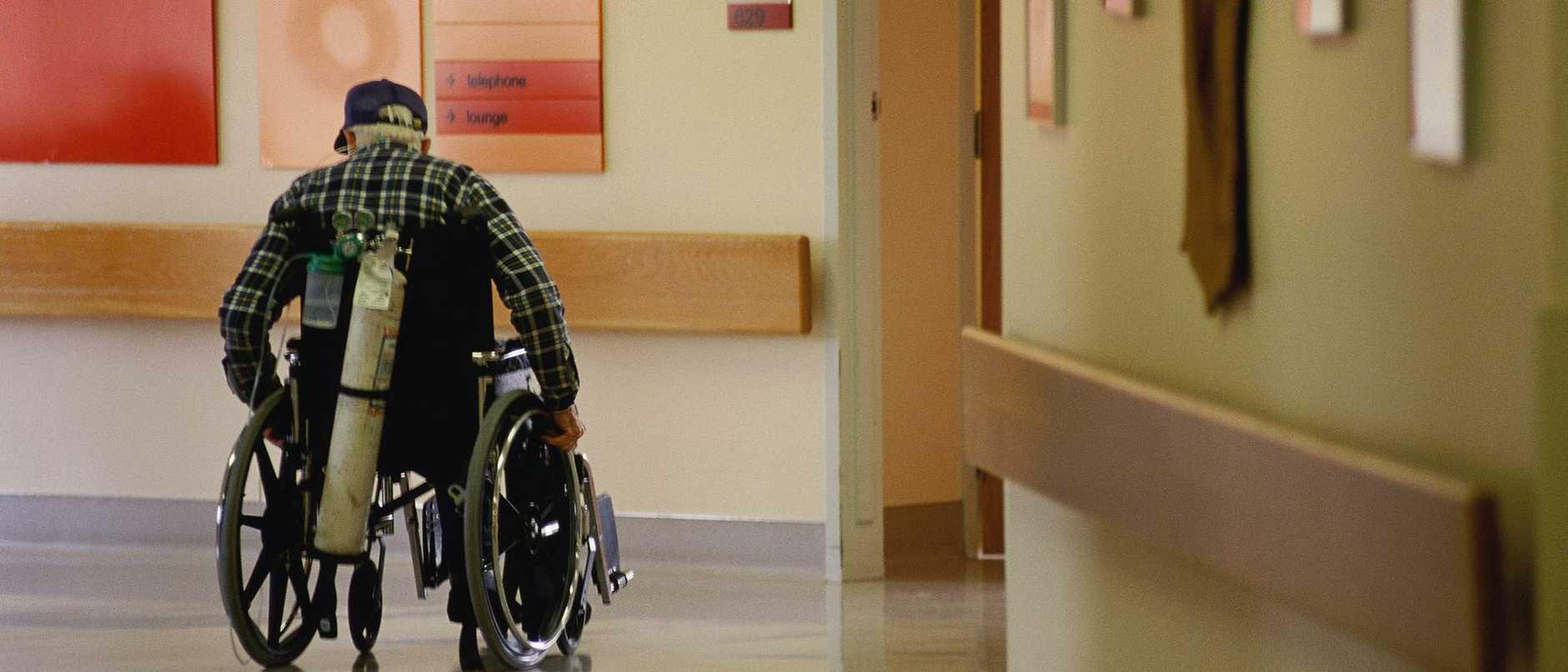 AGED CARE .. Elderly man in hospital corridor in wheelchair, oxygen tank on back