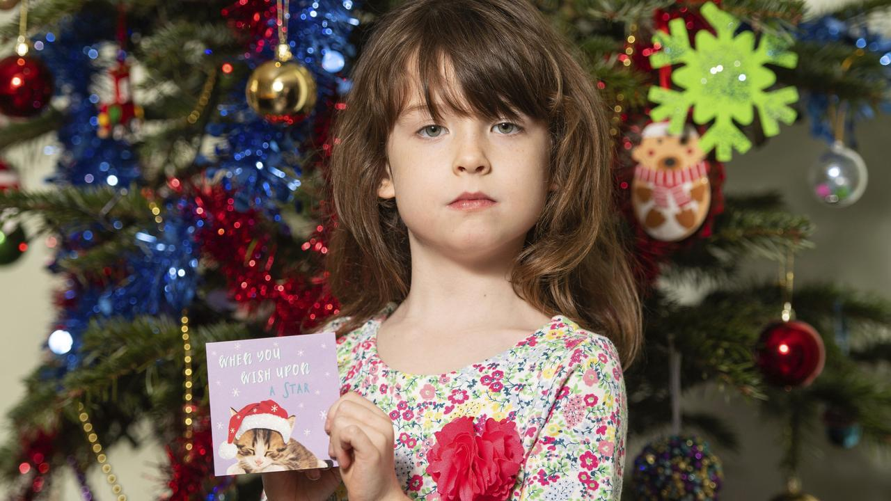 Florence Widdicombe, 6, poses with a Tesco Christmas card from the same pack as a card she found containing a message from a Chinese prisoner. Picture; Dominic Lipinski/PA via AP