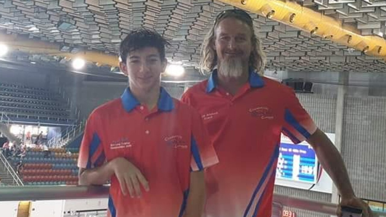 Jacob Bell, who made his state swimming debut at the 2019 McDonald's Queensland Championships, with coach Mark Erikson.