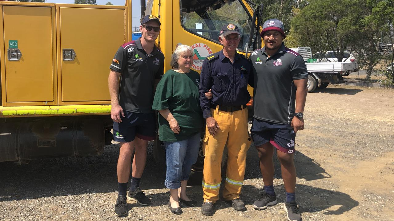 HELPING HAND: Queensland Reds players Bryce Hegarty and Brandon Paenga-Amosa (far right), with Barry Dyer of the Widgee Rural Fire Brigade and his wife Jenny Dyer last month. Photo: Contributed