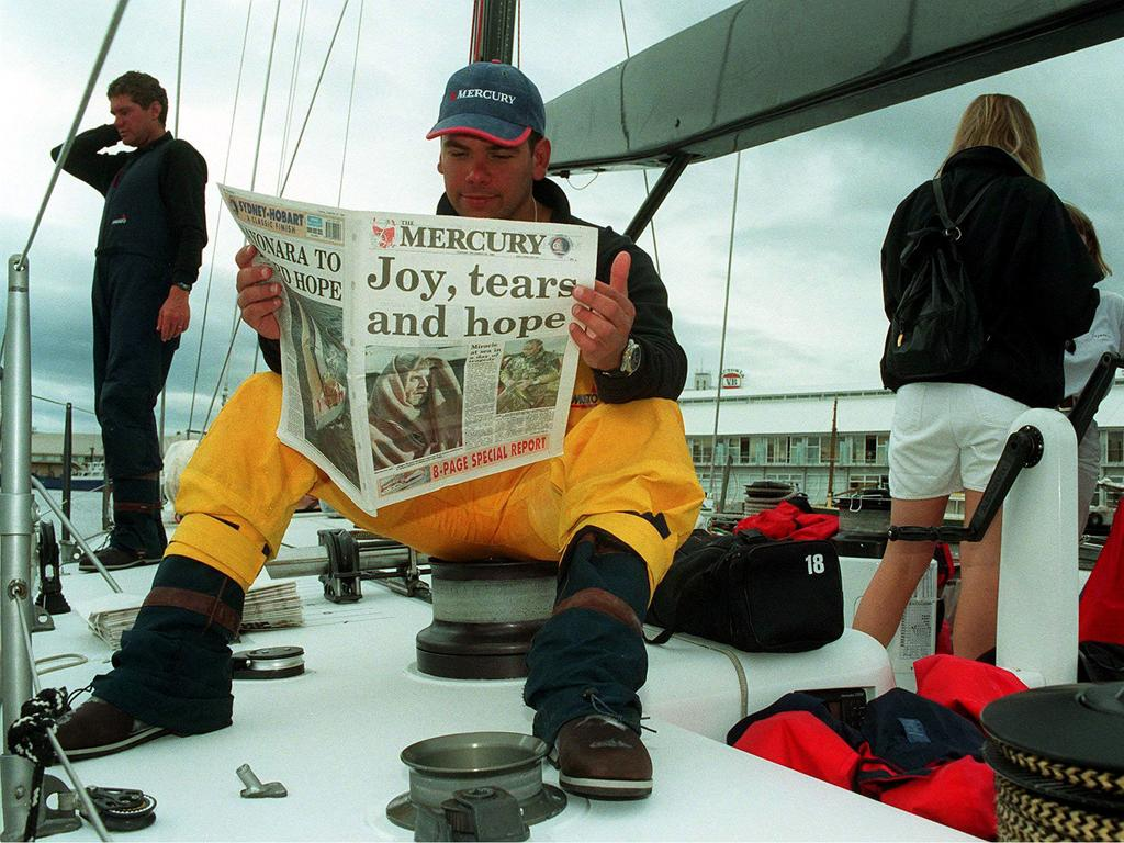 Lachlan Murdoch reads the newspaper on arrival at Constitution Dock aboard yacht Sayonara.
