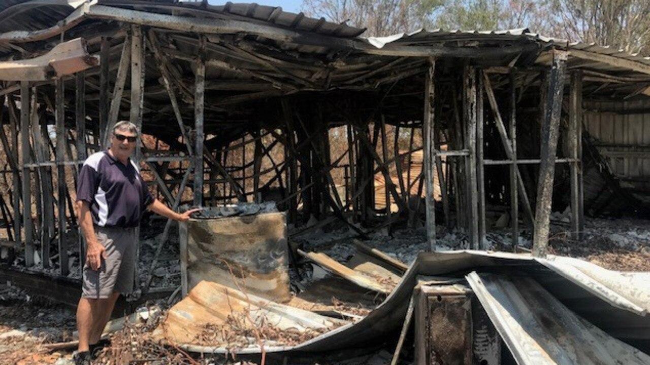 BUSHFIRE HERO: Vinnies volunteer Rick Williams in front of a Yeppoon home destroyed by bushfire.