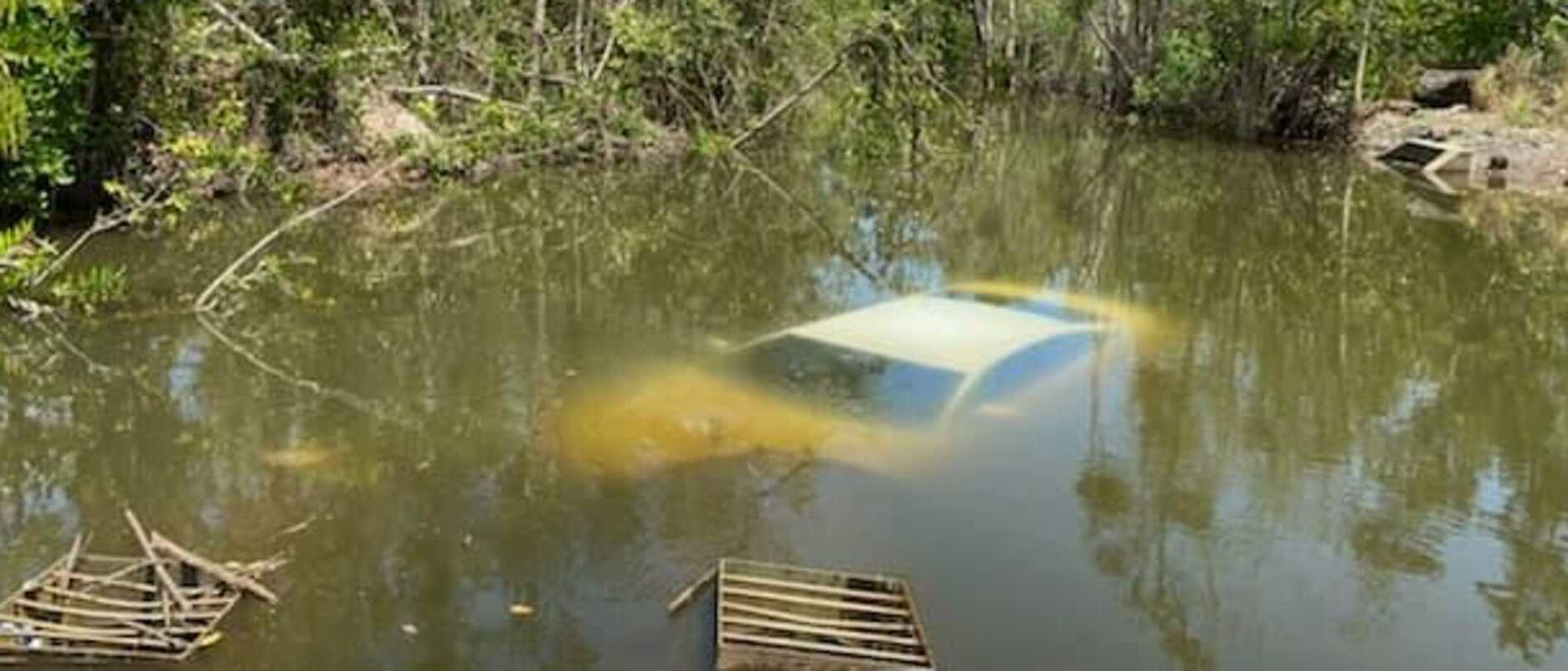 A car has crashed off a bridge and sunk to the bottom of a crocodile-prone waterway.