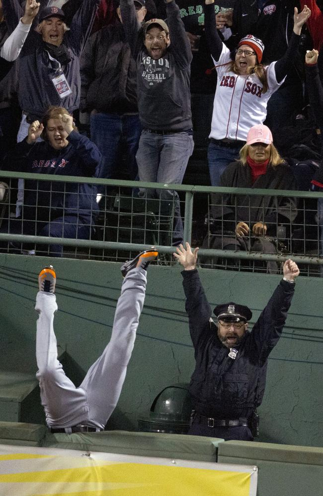 Boston Police officer Steve Horgan celebrates as the Detroit Tigers' Torii Hunter falls over the right field fence into the bullpen trying to catch a grand slam hit by Boston Red Sox' David Ortiz during Game 2 of the American League baseball championship series, in Boston. (AP Photo/The Boston Globe, Stan Grosfeld)