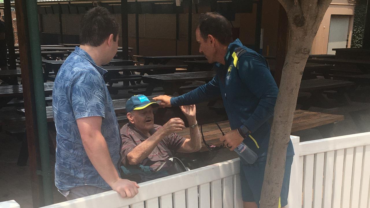 Australian cricket coach Justin Langer gives fan Bill Dean, 80, a cap at training.