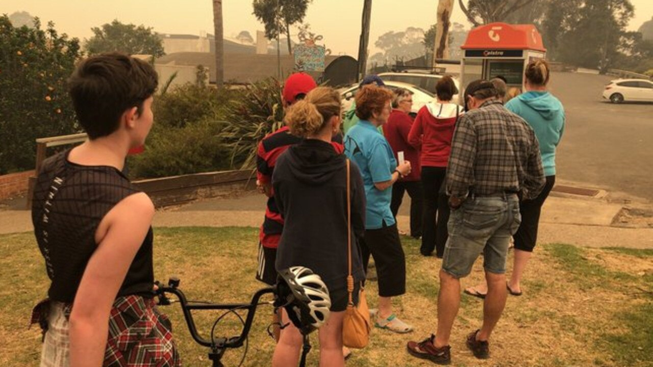 Bushfire-affected residents line up to use public phone. Picture: Jade MacMillan/ABC