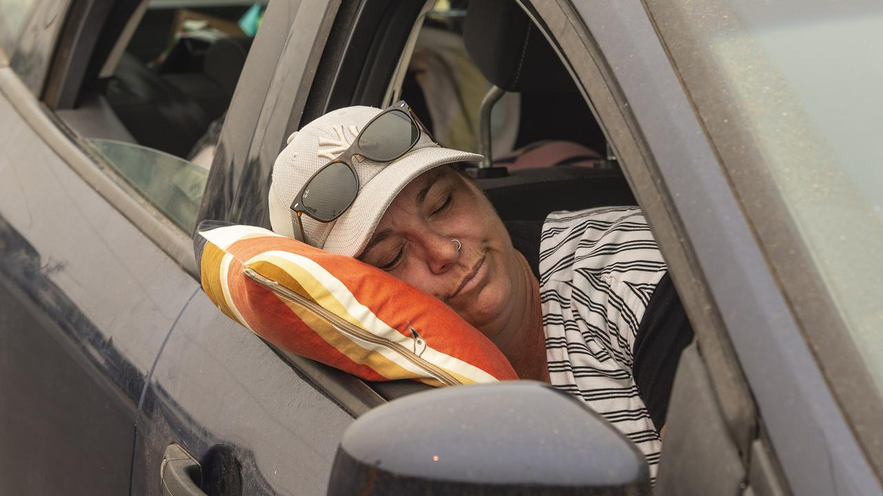 Naomi Lavery from Orange slept while waiting in a 1000m queue for petrol at Bermagui. Picture: Gary Ramage