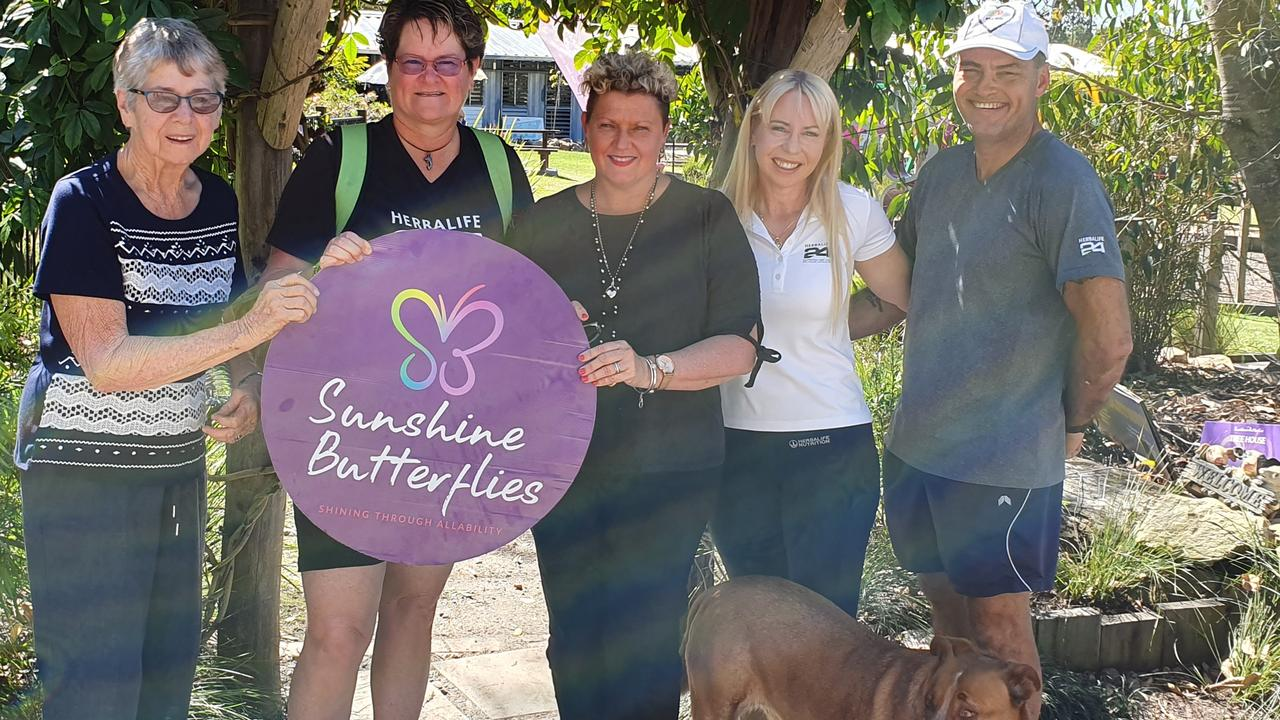 Sharon Milne, second on during one of her visits to Noosa's Sunshine Butterflies with Leanne Walsh, centre.