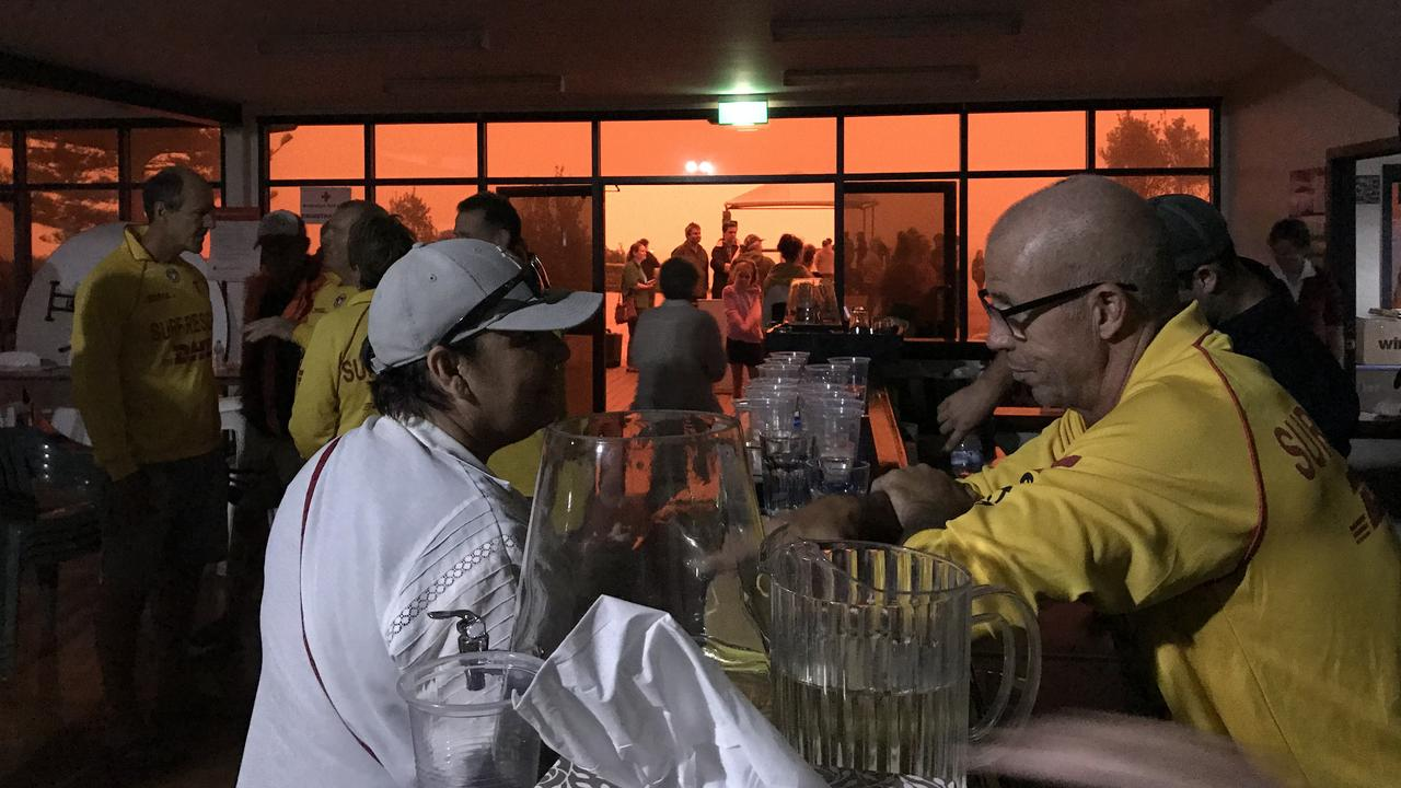Maroochydore Surf Life Saving member Stephen Lucas assists at Bermagui Surf Club. The glow outside is the reflection of the fire in the smoke.
