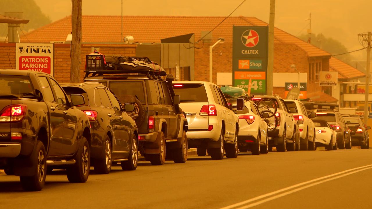 People queue for petrol in the smoke at Merimbula after bushfires cut off the entire south coast of NSW. Picture: Stuart McEvoy
