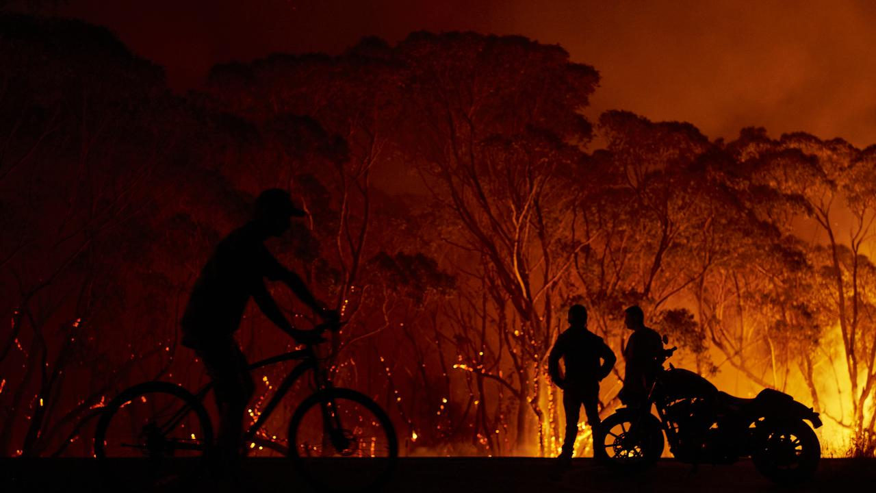 Residents look on as flames burn through bush yesterday in Lake Tabourie, in southern NSW. Picture: Brett Hemmings/Getty Images.