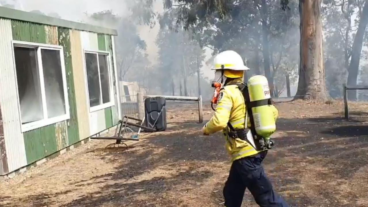 Dramatic footage shows former prime minister Tony Abbott running into a burning house to save homes during the NSW south coast's horrific bushfires. Picture: Ingleside RFS