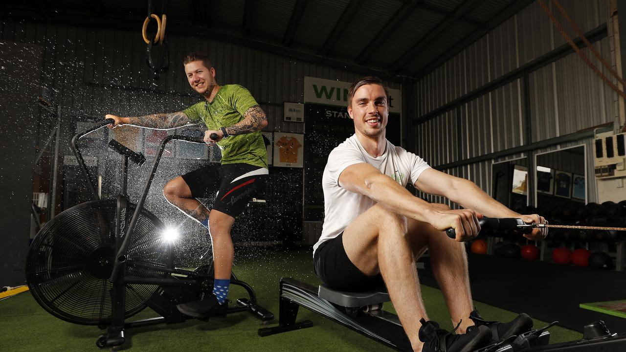 Giles Aldridge and David Lawrence posing at Winkfit, Brisbane, 5th of January. They're rowing and cycling on the 19th to raise money for the bush fire appeal. (AAP Image/Josh Woning)