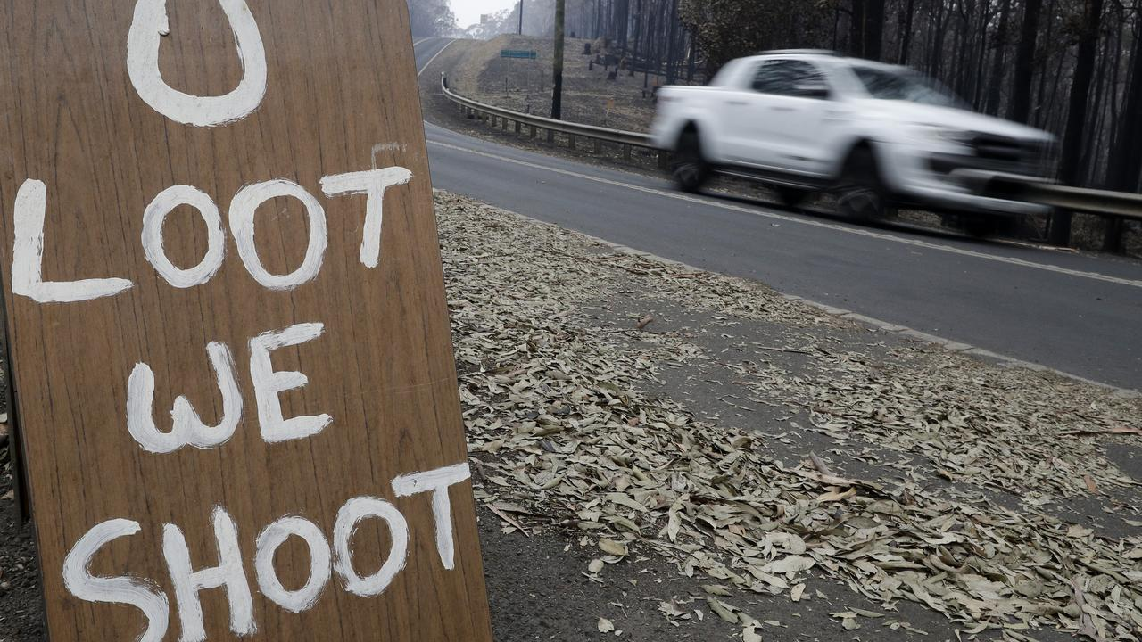 A sign discourages looters near Conjola Park, NSW. Photo: Rick Rycroft/AAP
