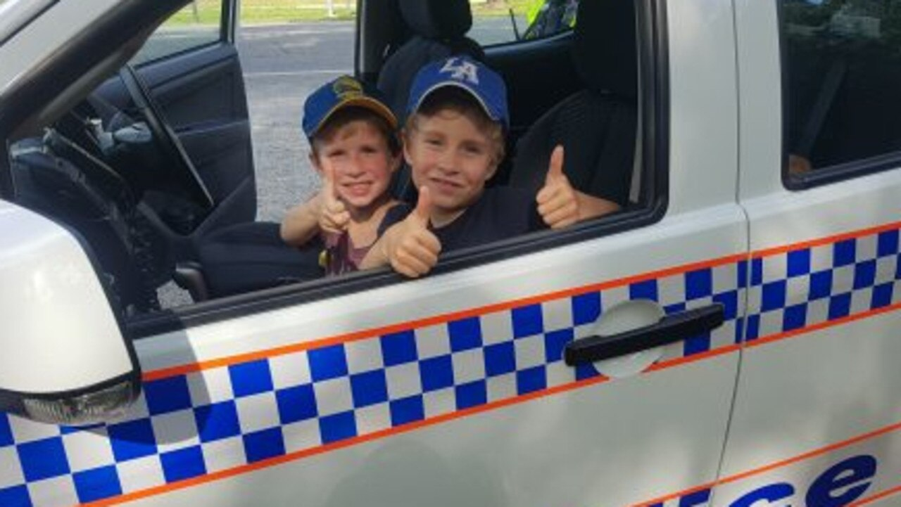 Jack and Will Reilly take a breather in the police car after a tough day of lemonade sales. Picture: Supplied
