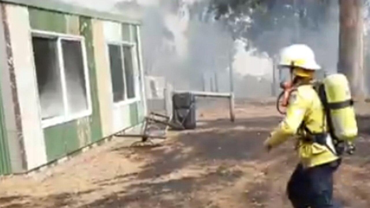 Former Australian prime minister Tony Abbott, wearing breathing apparatus, runs towards a burning building in Bendalong on Saturday. Picture: Ingleside RFS