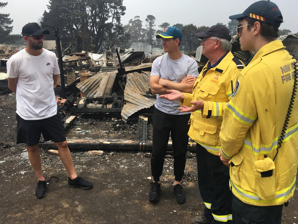 Test cricketers Tim Paine and Nathan Lyon on the fire ground with Ku-ring-gai Brigade deputy captain John Corry and RFS volunteers at Wingello. Pictures: RFS