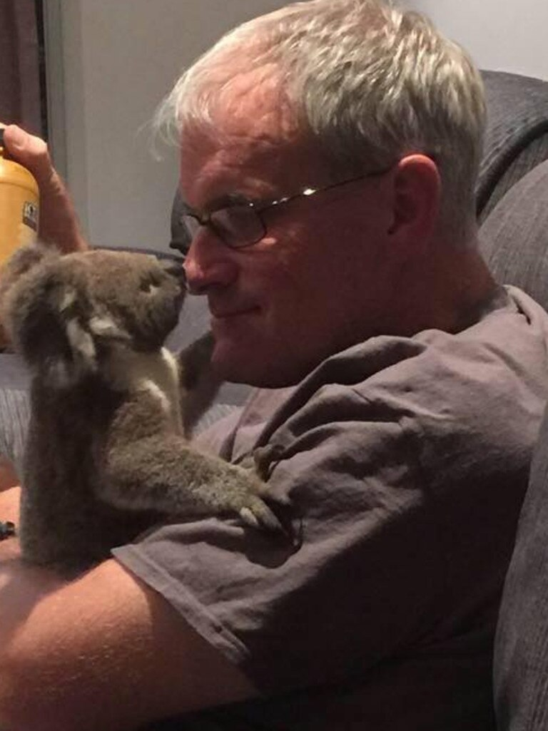 Peter Luker, 55, with a koala joey rescued following a bushfire in Queensland in December. Picture: Peter Luker