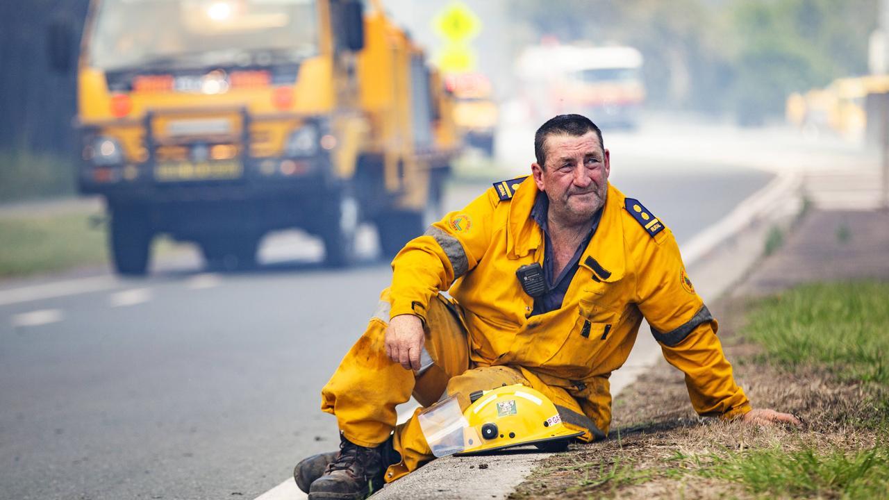 Rural firefighters stop to catch their breath as a wild bushfire roared towards Peregian. Photo: Lachie Millard