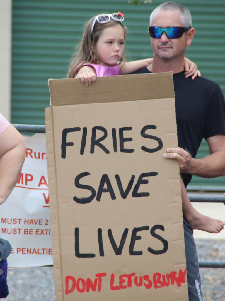 "Members of the Captain Creek community members hold a sign saying ""Firies Save Lives - Don't let us burn."""