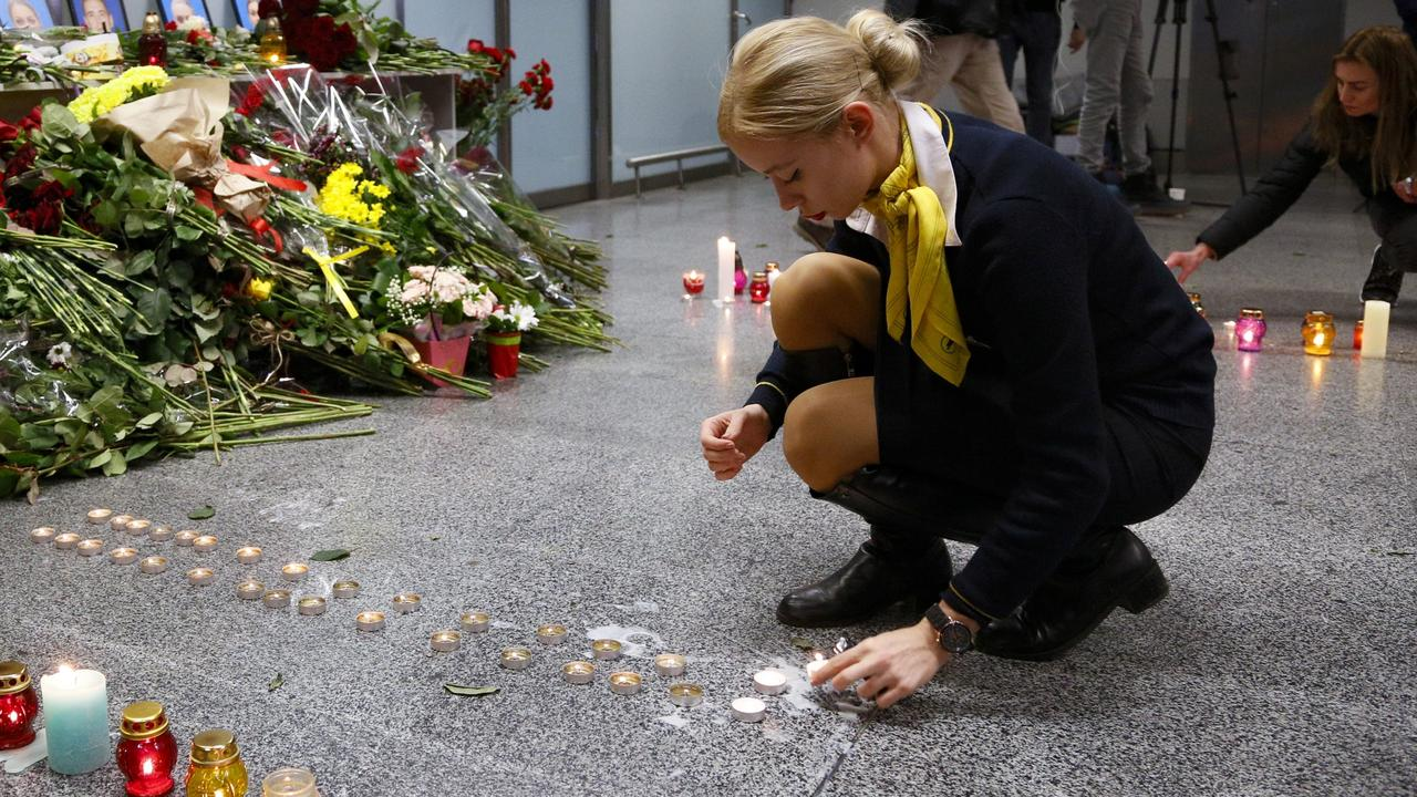 A colleague of one of the flight crew members of the Ukrainian 737-800 plane that crashed on the outskirts of Tehran, lights candles at a memorial inside Borispil international airport outside Kiev, Ukraine, on, January 8, 2020. Picture: AP /Efrem Lukatsky.