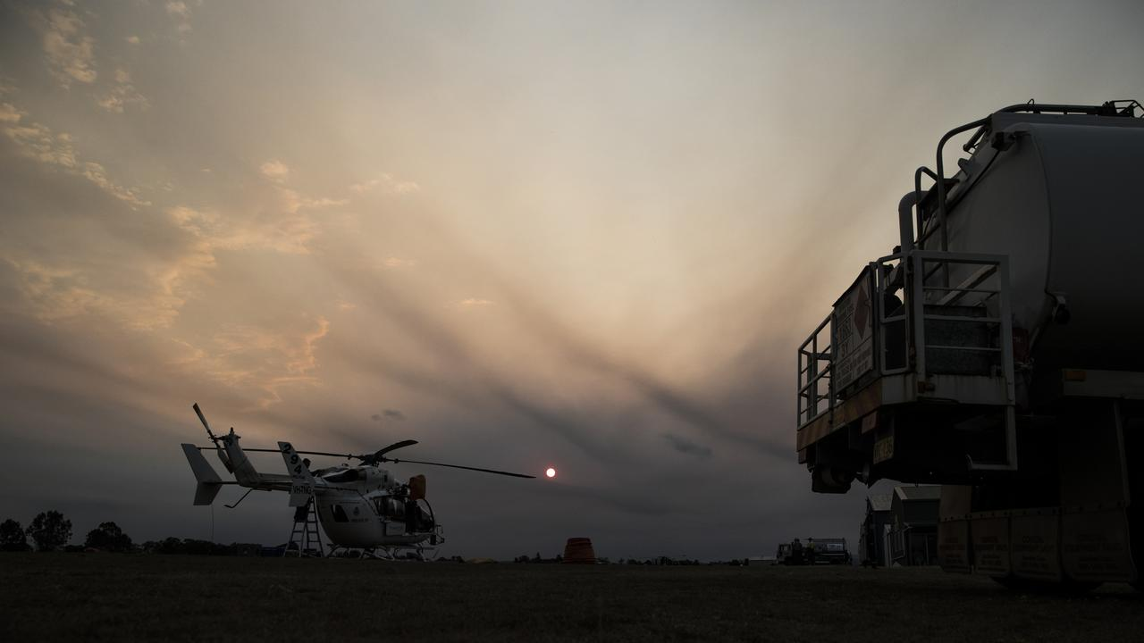 NSW RFS helicopter sits on the ground as the sun begins to set behind heavy smoke seen from Casino Airport and NSW RFS Control Centre. Picture: Dylan Robinson/file