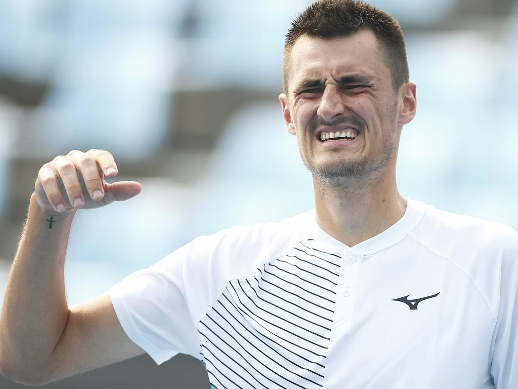 Bernard Tomic grimaces as he lifts his injured hand during his match against Denis Kudla.