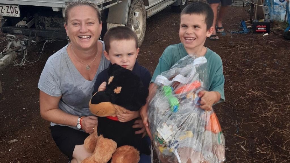 SPREADING KINDNESS: Darleen McAllan from the Gold Coast gives Lachlan, 3, and Patrick, 7, presents during her visit to Dumaresq.