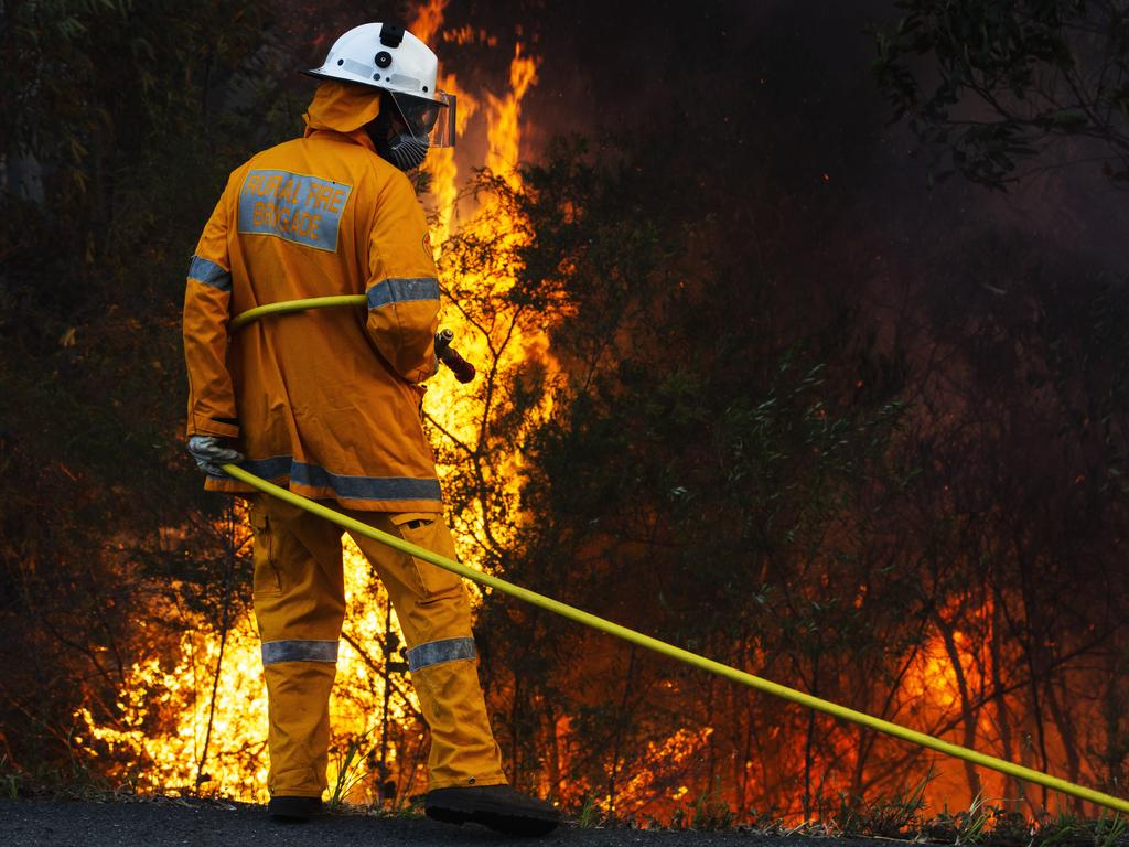 Rural firefighters work to control a blaze near the Sunshine Coast motorway that threatened a number of homes near Peregian Springs and forced residents to evacuate near Lake Weyba. Picture: Lachie Millard