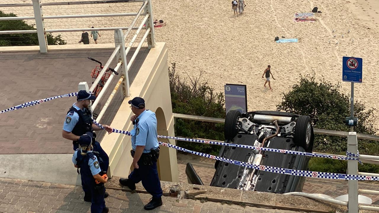 A car has crashed on to its roof on the walkway near Icebergs at Bondi Beach. Picture: Mark Morri