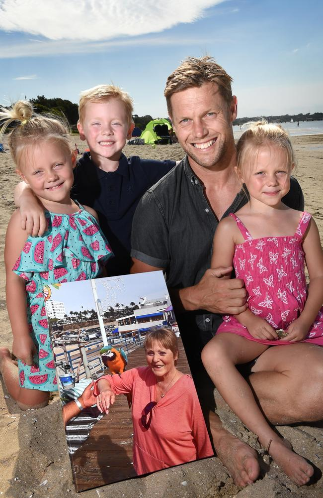 Sam Mitchell with his children, Smith, Emmy and Scarlett holding a photo of his mother-in-law, Valda. Picture: Tony Gough