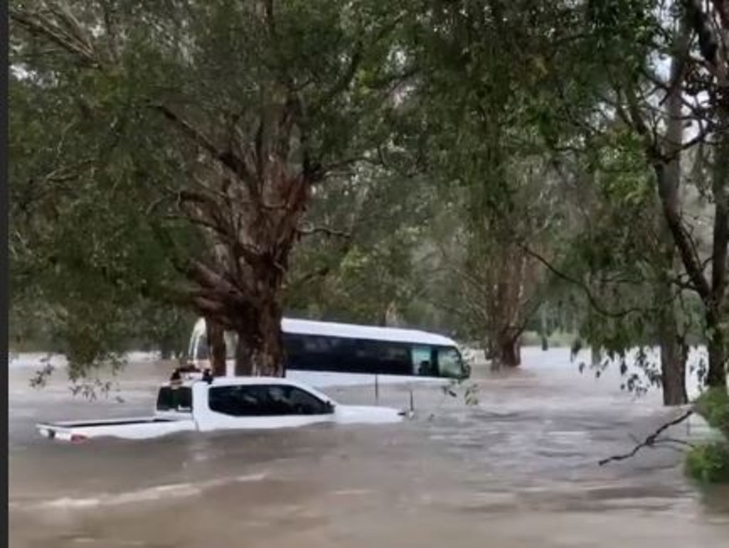 A mini bus is swept away and a ute is underwater at the Big 4 Caravan Park at Helensvale. Source: RNR Wanderers