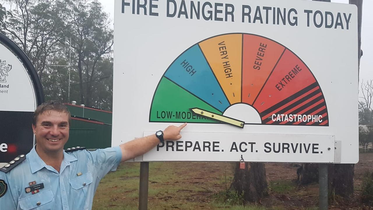 WONDERFUL SIGHT: Rural Fire Queensland Acting Inspector Jon Welke smiles in the rain as he changes the fire warning at Cabarlah to